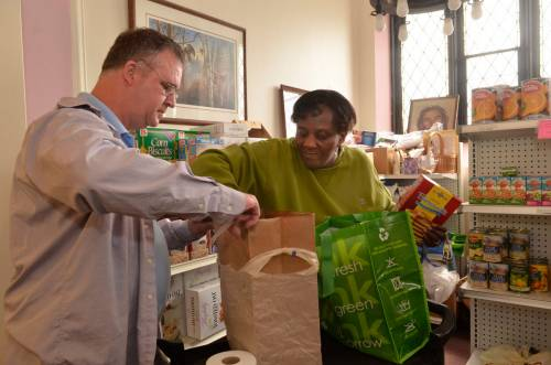 Keith Jakway, Geddes, NY, volunteer at the First United Presbyterian Church food pantry on West Genesee St in Syracuse, assisting Syracuse resident Bonnie Warren with her food needs.