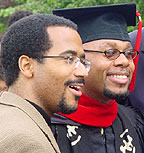 Photograph of two men, one in graduation robe and hat.