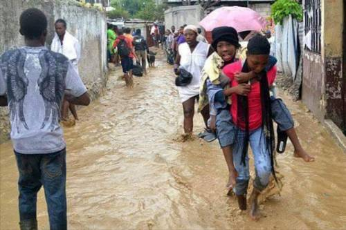 A survivor is carried to safety through a flooded street. (Photo courtesy Lutheran World Federation, Haiti)
