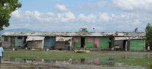 """El """"barrancon"""" de Batey 7 donde ayudó el grupo de visitantes de la Iglesia Presbiteriana de Westminster (Greenville, SC). Un barrancon es un edificio dividido en varias habitaciones, en este caso 10 en frente y 10 detrás. Originalmente eran para los cortadores de caña que el presidente de la República Dominicana traía de Haití hace 40 años. Ahora son familias que viven en las habitaciones, aveces una familia completa por habitación. En esta foto, el grupo de los voluntarios de los Estados Unidos y el grupo de voluntarios del Comité de Desarrollo Comunitario acaban de terminar de quitar toda la basura innecesaria de los techos."""