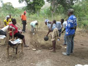One-day workshop in the community of Gwanit, where Road to Life Yard team member Durosier Joachim (left side of bed with hoe) shows participants how to finish a raised bed.