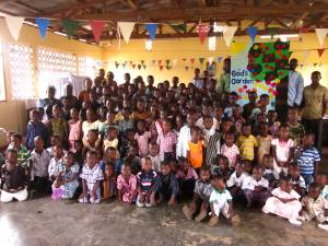 "The children of one congregation in rural Ghana gathered around a banner (back right) that reads ""God's Garden"""