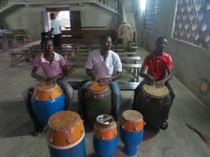 Men from the young adults of the church, playing the drums as choir practice is about to start.