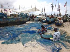 Fishermen in Ghana mending their nets, after a long day out at sea