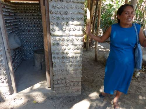 Gloria, in front of a latrine made of recycled materials, sharing with us the success of her family garden