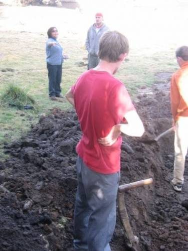 Angelica gives instructions to Jed as volunteers from the U.S. help in the construction of an irrigation system.