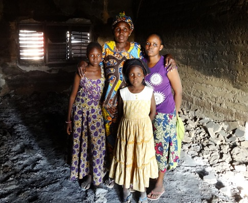 A Christian family standing in their house that the mob burned
