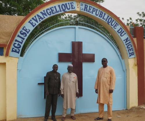 The president of the EERN, the pastor from Zinder, and another church leader stand in front of the new church gate