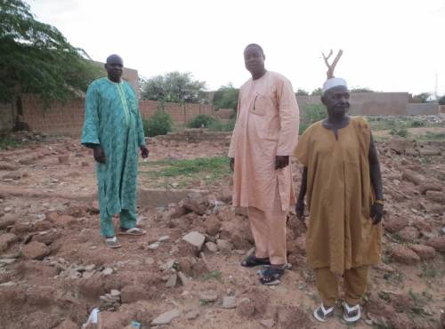 The new pastor, a national church leader, and the old pastor stand on the rubble of the Mirriah church