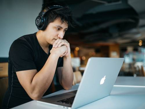 Young man in taking an online course using his laptop computer.