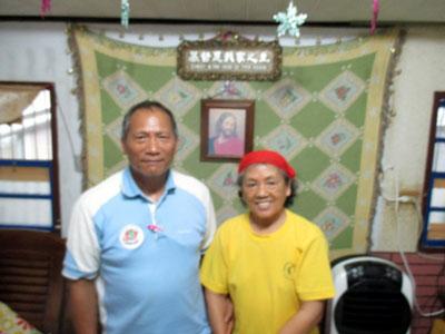 Elder and Mrs. Bavan in their living room