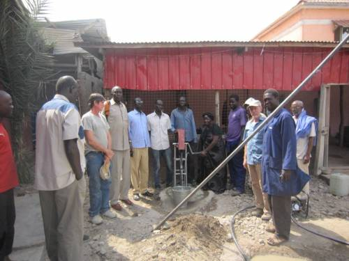 Rev. Paska turning a water pump at a training site in South Sudan