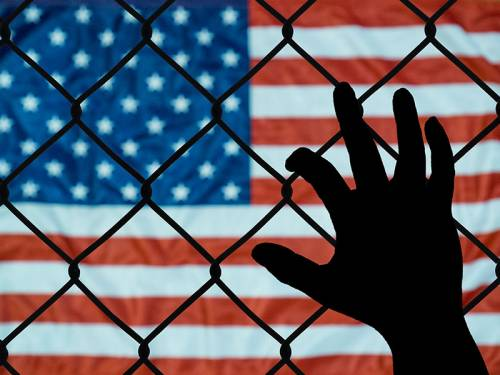 U.S. flag shown through a chain-link fence with a migrant's hand holding the fence.