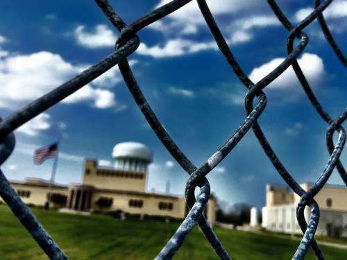 Looking through a chain link fence at the Flint water tower.