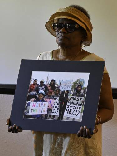 Woman holding photo of children.