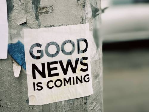 Sign attached to pole that reads: Good News is Coming