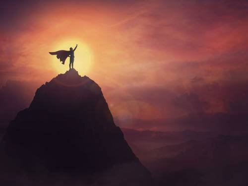 """Image of """"superman"""" type figure with a cape standing on top of a mountain"""