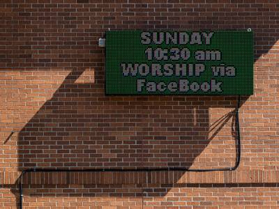 Photo of outside wall of church with sign that says Sunday Worship will be on FaceBook
