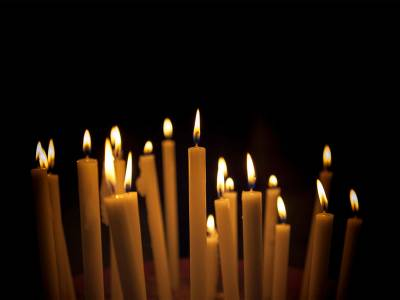 A bunch of lit candles against a black background.