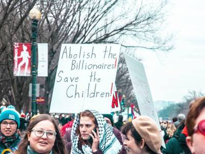 "Protesters carrying sign that reads, ""Abolish the billionaires! Save the children!"""