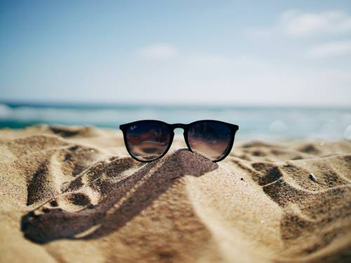 Pair of sunglasses resting on the sand at the beach.