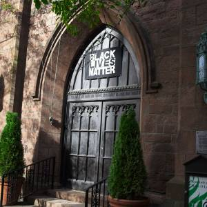 A Black Lives Matter sign over a church door entrance.