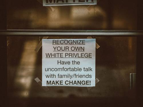 Sign taped to window that says: Recognize Your Own White Privilege: Have the uncomfortable talk with family/friends. Make Change!