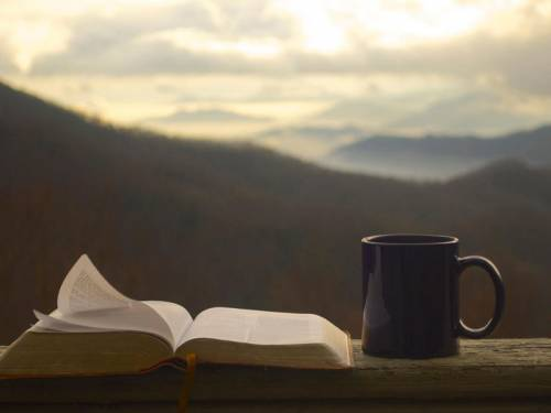 A view of the mountains in the background with a Bible and a coffee mug.