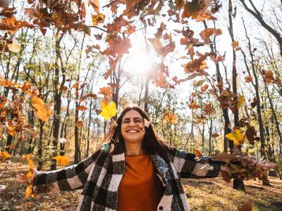Smiling woman with arms outstretched as leaves are blowing all around her