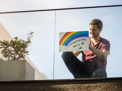"Man holding sign outside window with rainbow and message that reads, ""Everything will be OK."""