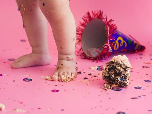 Toddler walking through cake and glitter after a party.