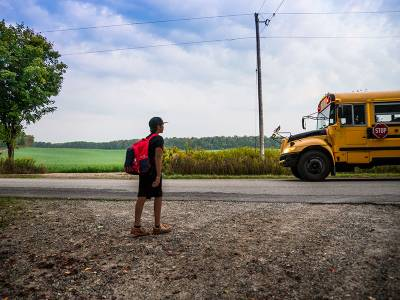 Child of color waits for a school bus in a rural area.