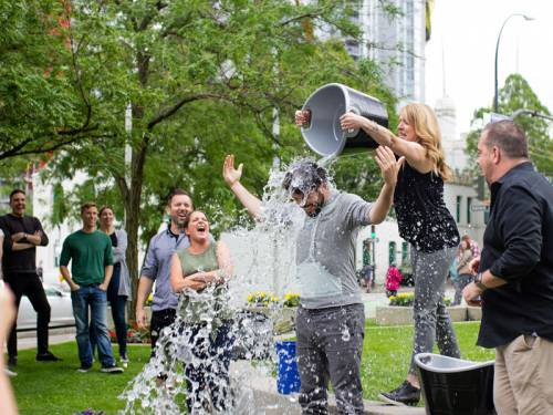 Woman pours a bucket of water over a man's head during a fundraiser