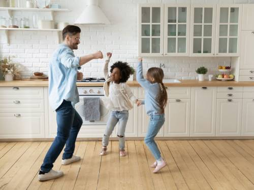 Father and his two children dancing in their kitchen