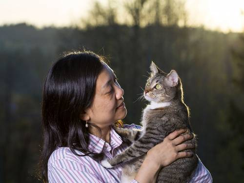 Woman holding cat and smiling