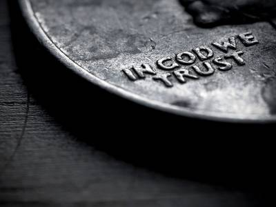 """Close-up of U.S. coin showing the words """"In God We Trust"""""""