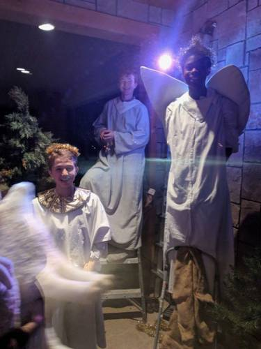 Smiling children in angel outfits - long white robes with wings - participate in the living Nativity.