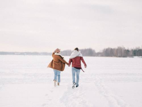 Couple walking hand-in-hand in the snow.