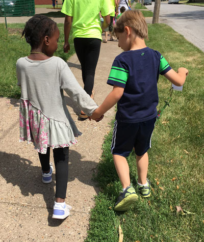 young children walking and holding hands