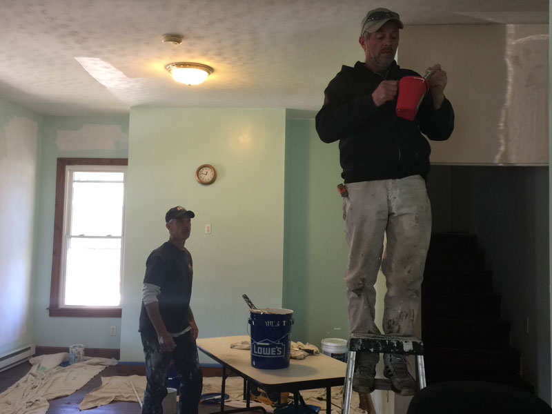 The men of Advocate House take charge of the home's renovations, painting the living room area. They are also responsible for a weekly deep clean that includes kitchen and bathroom areas. (Photo by Sue Washburn)