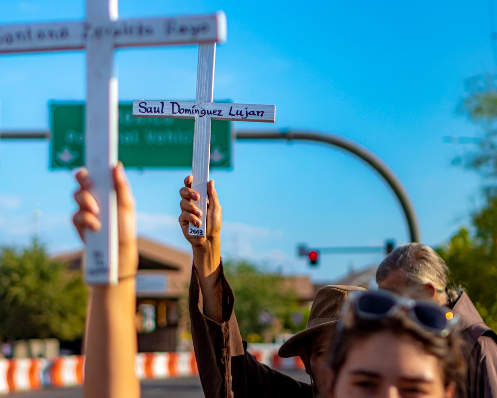 People attending the Healing Our Boarders vigil hold crosses before the U.S. Customs and Border Protection building. (Photo: Eric O. Ledermann)