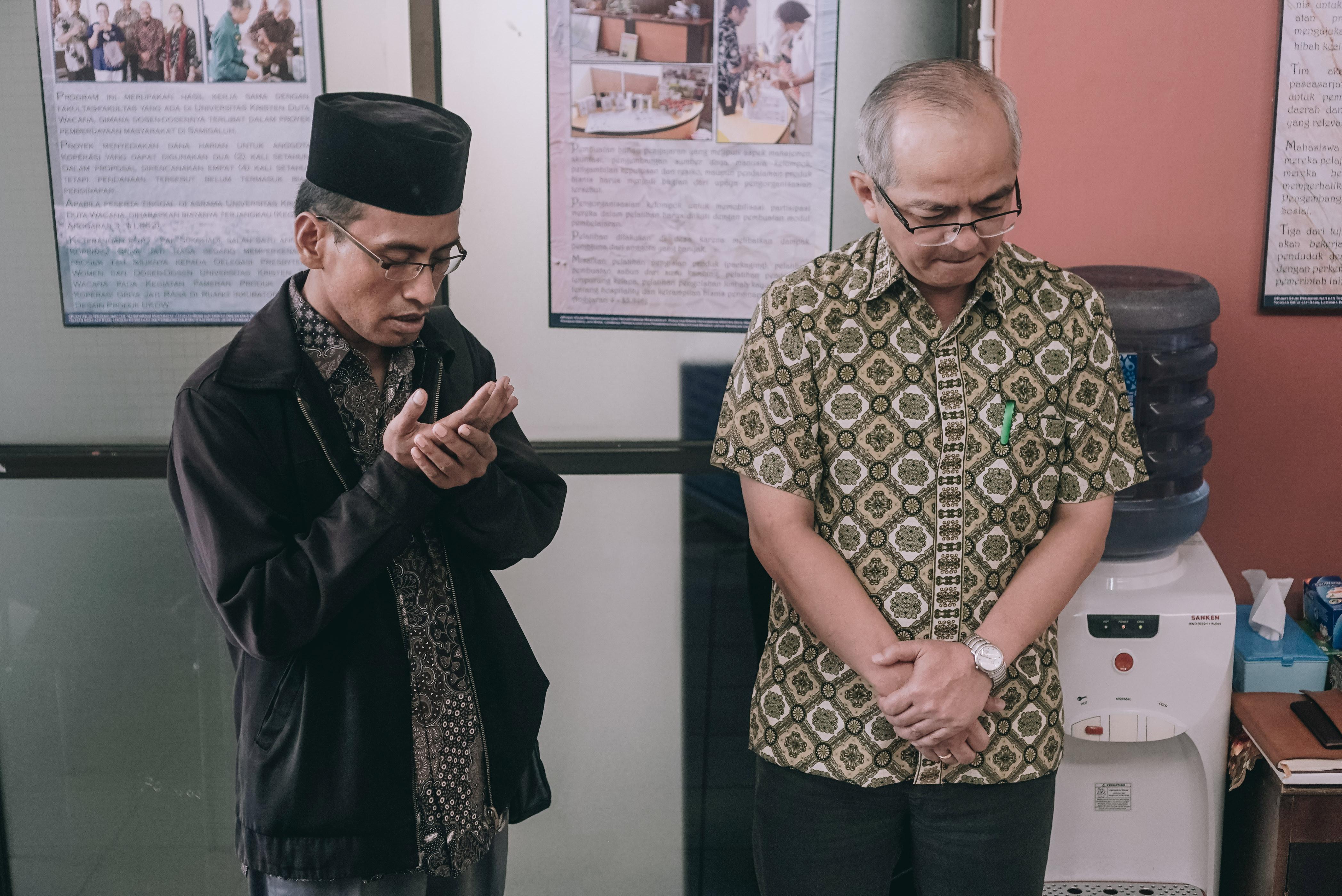 Ustad Benny leading prayer alongside Henry.