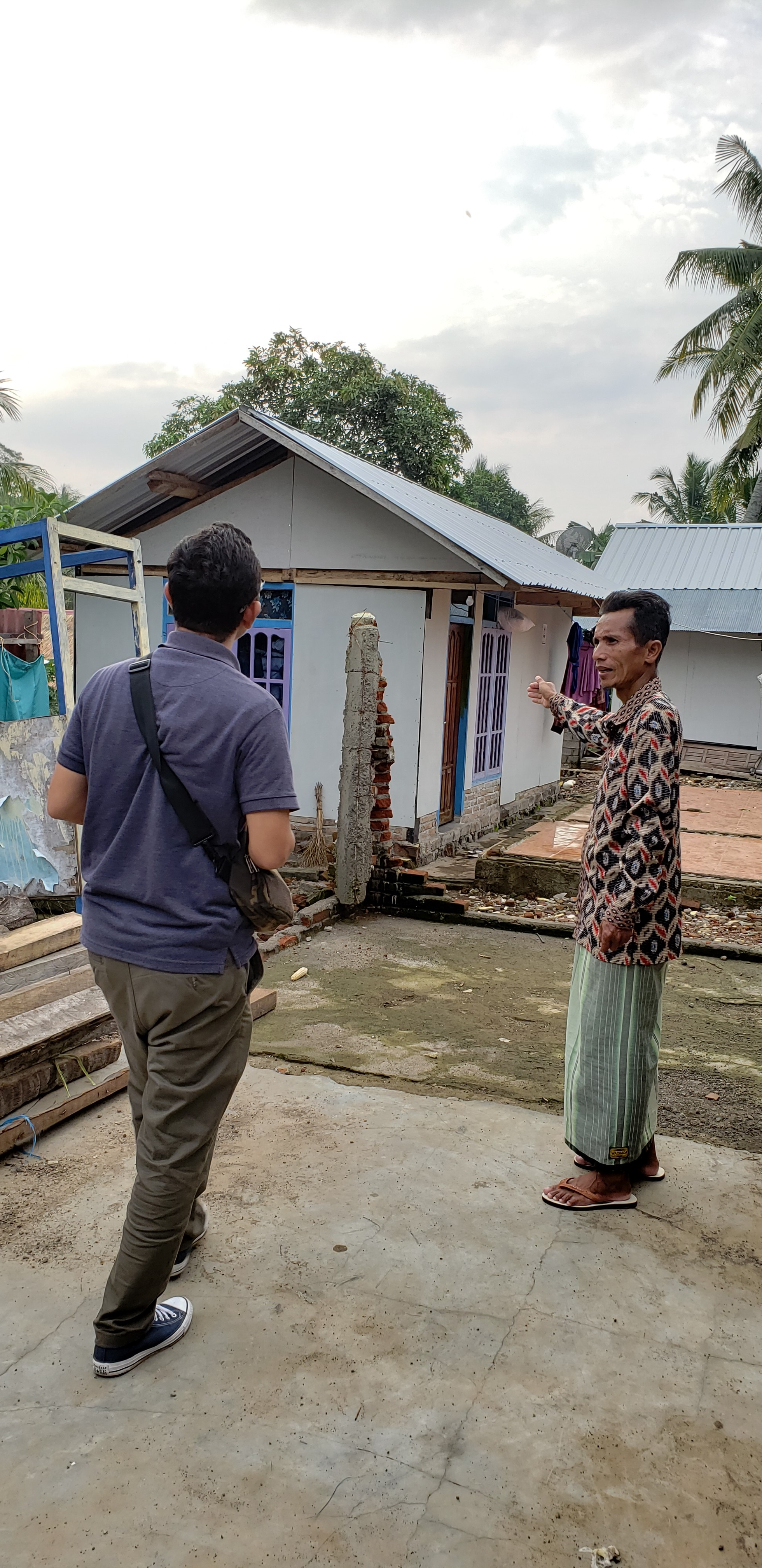 A leader in a village damaged by an earthquake shows the impermanent houses to my student.