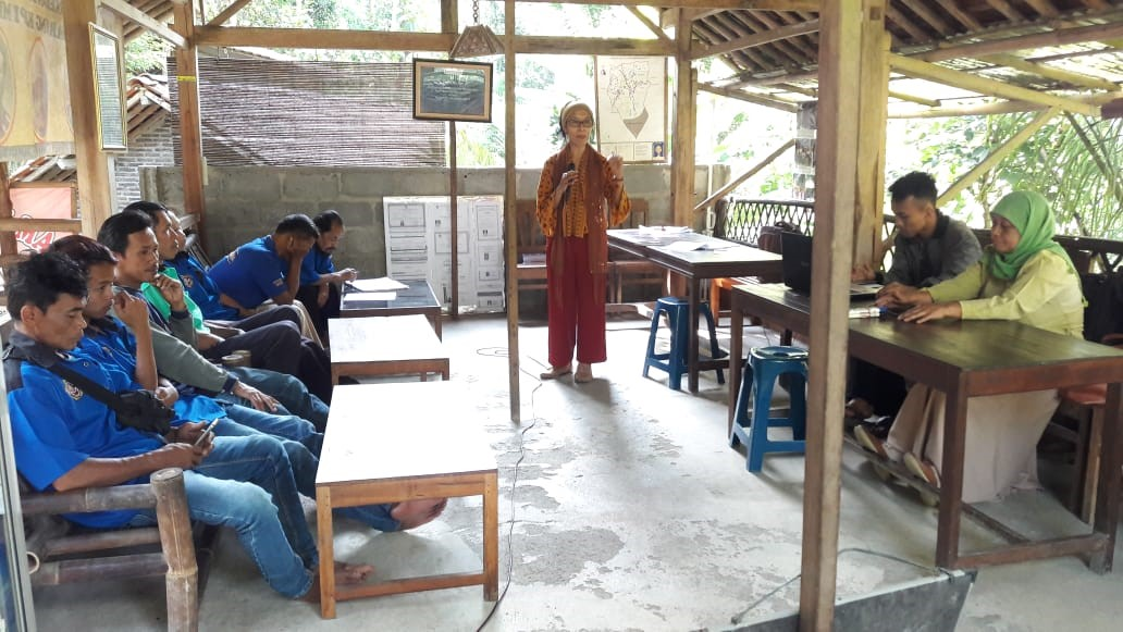 Farsijana instructing participants on how to operate the coffee-processing machines.