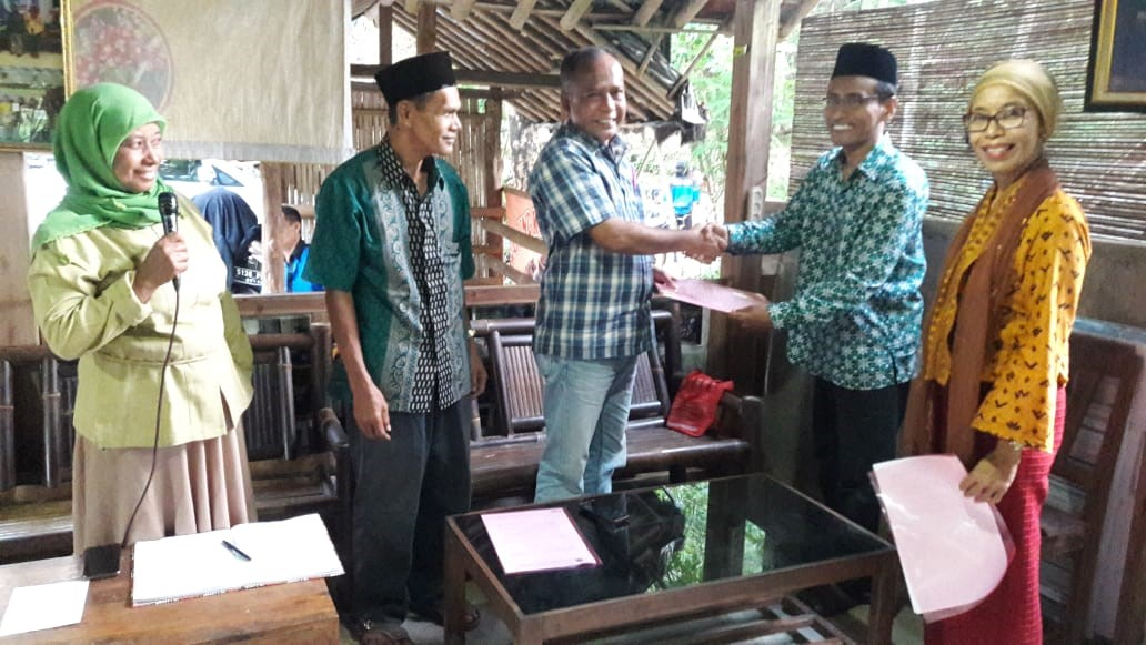 Benny Susanto shakes hands with the head of Sidoharjo village in the Samigaluh district. The two also exchanged a Memorandum of Understanding (MOU), making official the HAS Co-op's relationship with the village. Mrs. Marwiyah (far left) speaks to the importance of this relationship.