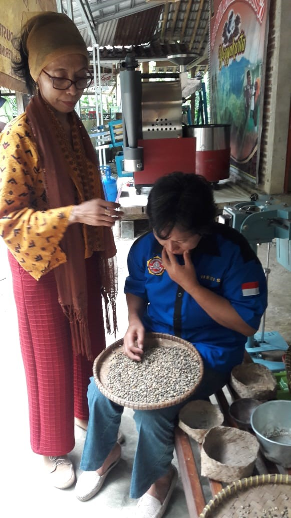 Farsijana with a Christian member of the HAS Co-op who is selecting coffee beans for roasting.