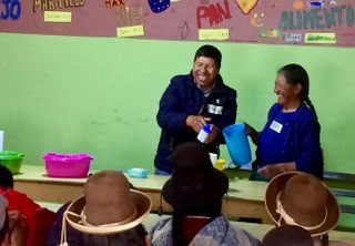 Women (in traditional hats) laugh with a participant in the nutrition and personal hygiene workshop as he demonstrates good handwashing.