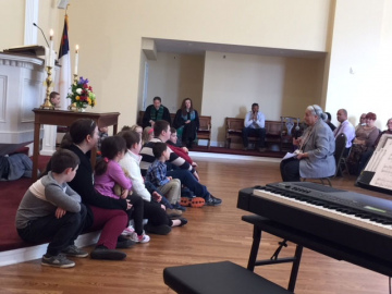 Both adults and children listen intently to the children's sermon.
