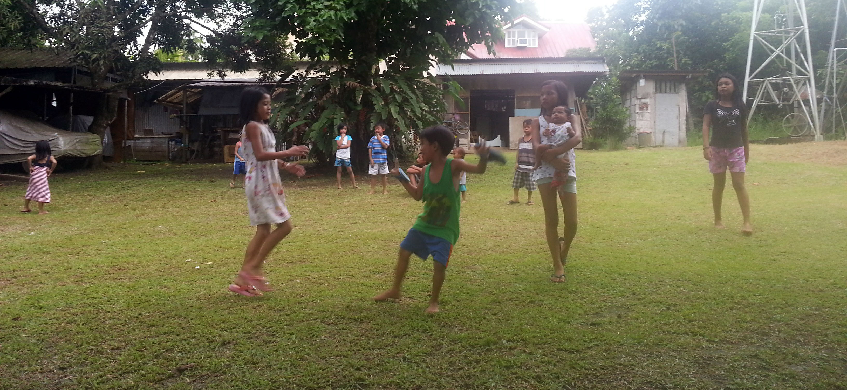 Children relax by playing tag and other games on the grass.