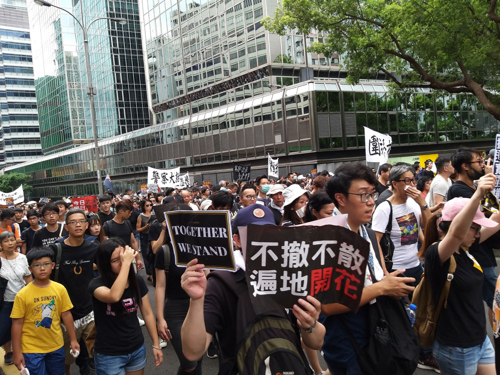 """A protest march. A message to the chief executive on the large sign in the front reads, """"If you don't leave, we won't leave. The protests will spread like flowers."""""""